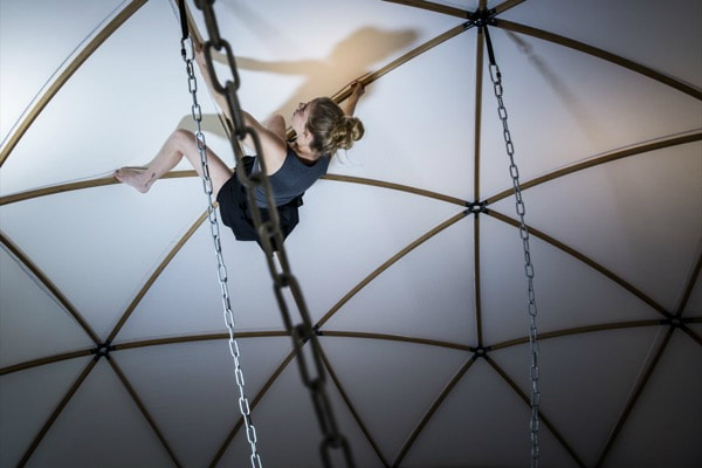 A photo of Agit Cirk's Jenni Lehtinen climbing across a tent at Brighton Fringe Festival's St Mark's Chapel spire in 2018