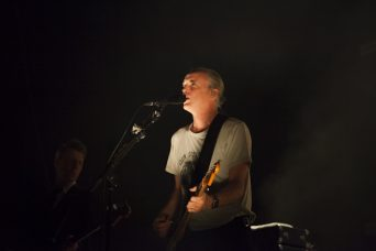 A photo of Fran Healy singing on stage while playing a guitar when as part of a Travis review at Brighton Dome