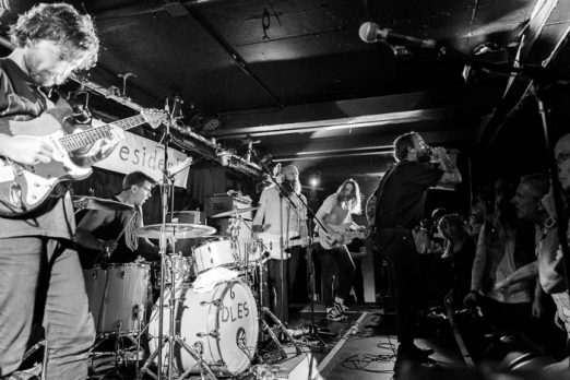 A photo of the band in a packed room in a photo by Sam Sesemann as part of an Idles review